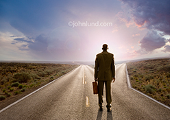 A businessman stands at a fork in the road, briefcase in hand, deciding which way to the future is the right choice in a concept stock photo.
