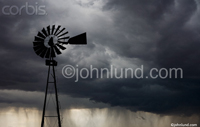 Pictures of  wind power; a windmill in a storm. Picture of an old fashioned windmill used for pumping water dark against storm clouds.