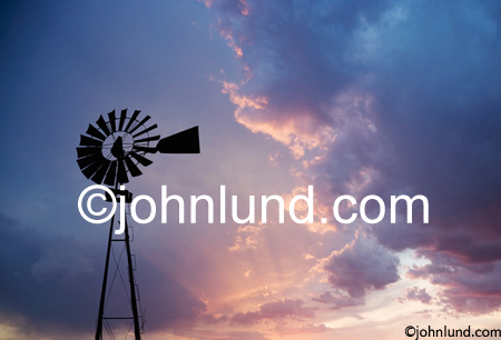 A windmill is silhouetted against a gorgeous sunrise show the dawn of a new age of windpower and renewable energy sources. Picture of an old windmill. A wind energy photo.