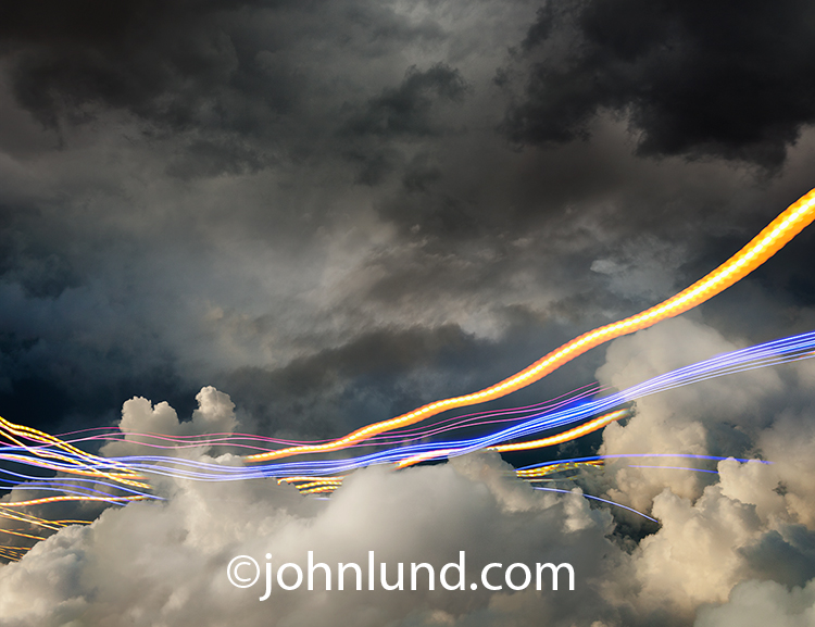 cloud computing and communications technology are both illustrated with this stock photo featuring vivid streaks of colored lights weaving through high altitude cloud formations.