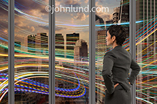 An African American woman business executive stands in a high rise office looking out over an urban scene filled with streaking colored lights in a metaphor for wireless communications, future communications technology, and social networking.