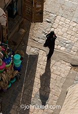 A Yemeni woman wears a traditional Abaya, a garment that covers her from head to toe, as she navigates a narrow street on the Old City of Saana.