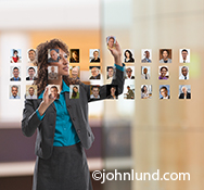An African American woman executive re-arranges photos using future technology in a stock photo about human resources, new hires, communications technology, online dating and social media strategy and participation.