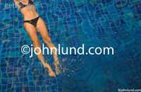 Picture of a womans torso on her back in a tiled swimming pool at a luxury resort spa photographed in Koh Samui, Thailand.