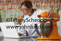 Hispanic woman chef using a laptop in the kitchen while she rests her hand on a bright orange mixer. She is wearing a white chefs uniform and she wears glasses.  Brown hair. Chef using laptop pic.
