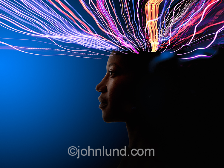 Connections, networking and communications technology are represented by this stock photo of a woman with streaming data engulfing her head.
