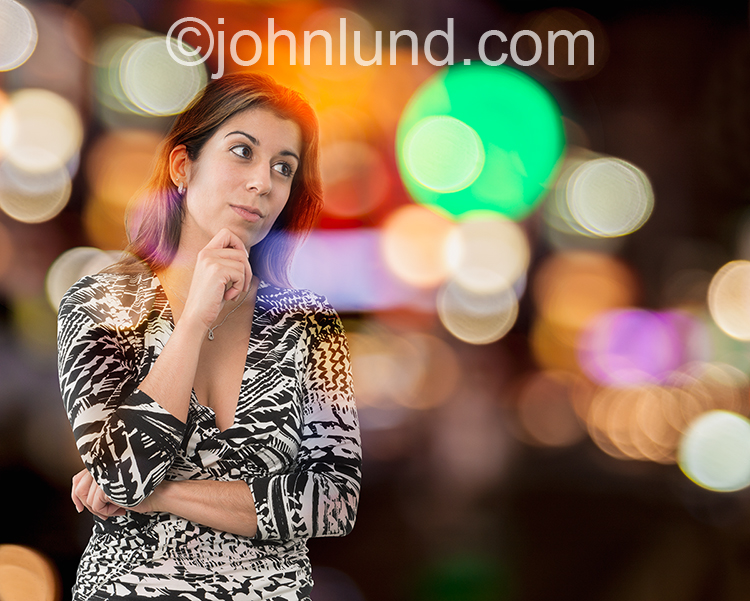 A woman contemplates business and the future against a backdrop of colored and out of focus city lights in an image about decisions, leadership and business concepts.