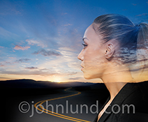 A woman contemplates the road to the future in a stock photo about the way forward, possibility, and journeys.