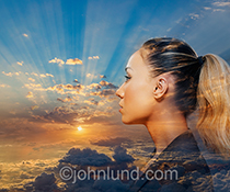 A woman contemplates life in this stock photo showing a woman superimposed over a high altitude sun rise complete with God Rays.
