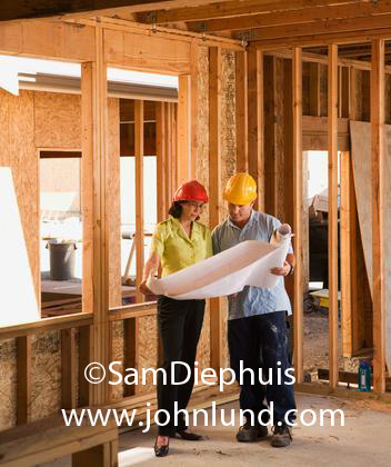 Picture of woman on jobsite. A woman wearing an orange hard had is conferring with a construction worker also wearing a hard hat over a set of blueprints they are holding together. The man and woman are standing amid bare exposed framing.
