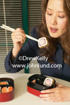 Photo of a Japanese woman using chopsticks to eat her sushi.  A pretty young adult Japanese or asian woman bringing up a piece of sushi to her mouth with her chopsticks. Pictures of sushi for advertising.