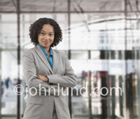 A mixed race woman executive portrait is situated in a large open glass building suggesting she is a global corporate leader.