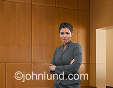 This executive portrait of an African American woman is siutated in an upscale wood-paneled corporate lobby.