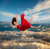 A woman in a red dress falls from a great altitude above the cloud level during a sunset in a conceptual stock photo about joy and letting go.