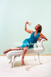 Beautiful African American young adult woman fanning herself with a handful of money. She is wearing a blue dress, and is reclining on a white love seat..