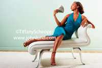 A hot sexy young black woman is reclining on a couch and fanning her face with a handful of cash. The woman is wearing a beautiful blue dress and is obviously flush with cash money.