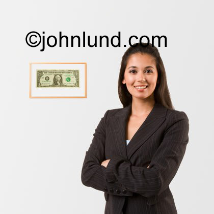 An Hispanic Business Woman Standing Beside a Framed Dollar. She had the first dollar she ever earned framed and hung on her wall.