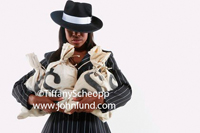 African American woman dressed in a fedora and a pin striped suit looking like an old time gangster is holding big bags of money with dollar signs on them.