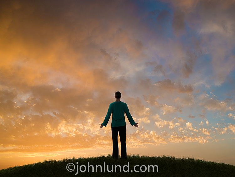 A woman faces a sunrise with outstretched arms in a gesture of honoring the miracle of life and the start of a new day.