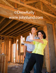 A man and a woman in a new home under construction. Woman is Imagining what her future home will look like. Home's interior is unfinished with just the framing and exterior walls completed. Advertising photos for new contstruction ads.