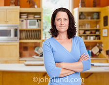 A successful and confident woman stands in the kitchen of her home in the portrait stock photo.