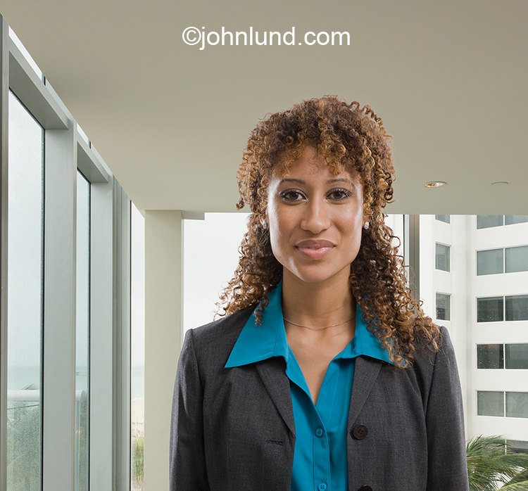 A smiling black woman's executive's portrait in an upscale corporate office shows confidence, ease and success.