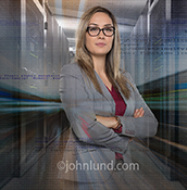 A confident woman executive stands in a server room in a composite stock photo illustrating the concept of women in technology, successful tech women, women in leadership positions and success women executives.