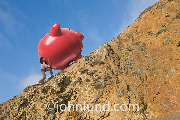 A woman investor pushes a giant piggy bank up a steep hill in this stock photo about women in finance, household savings, retirement planning, women's issues, and saving for the future.