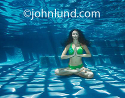 Picture of a woman meditating underwater in a swimming pool in a lotus yoga position as she pursues stress reduction in a unique and new age manner.