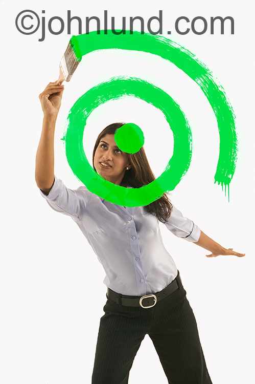 "A woman paints the concentric circles of a target in green paint in a stock photo about ""going green"", environmental goals, and ecological responsibility."