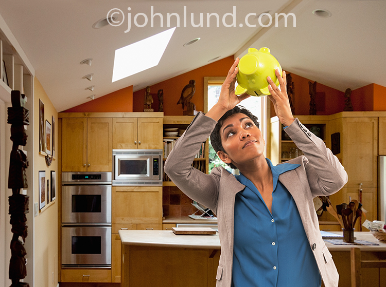 A woman in her home holds up a Piggy bank upside down and peers in to see if there is any money inside for an image about personal savings and investment.