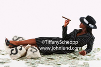 A young adult black woman is smoking a cigar, wearing a fedora, dressed in a pin striped suit, and laying in a pile of dollars and sacks of money.