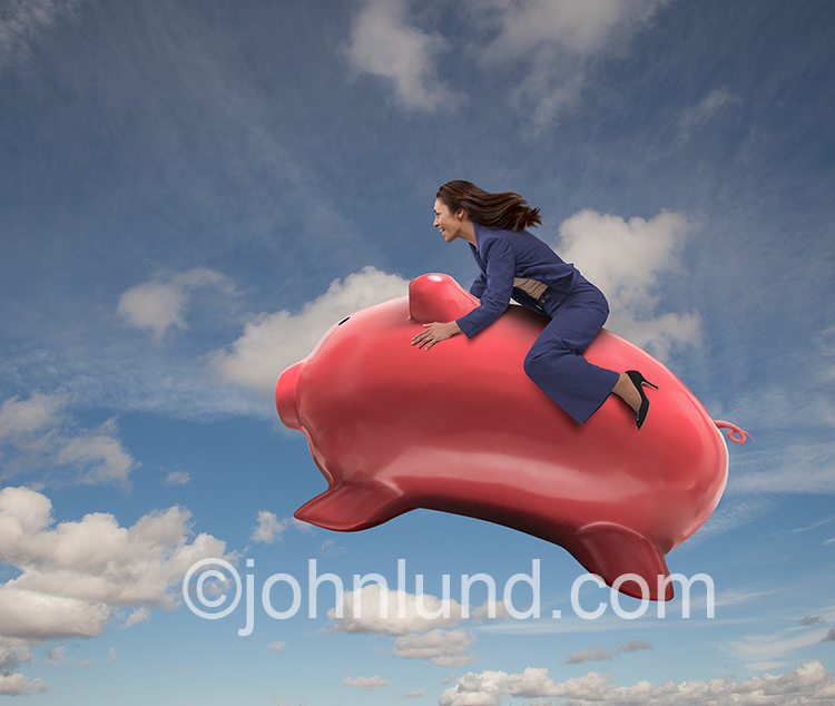 A woman rides a leaping piggy bank in a stock photo about savings, investment, financial planning and personal finances.