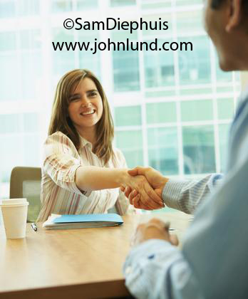 Picture of shaking hands. A woman executive sitting at her desk is reaching across the desk to shake a mans hand who is sitting across from her. Attractive young female executive shaking hands with a man. Woman facing camera man with back to camera.