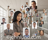 An Asian woman stands in a modern office surrounded by images of associates, friends and family in a picture of social networking, connections and teamwork.