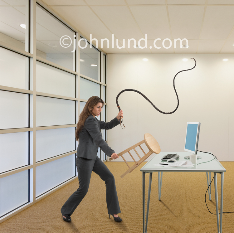 A woman holds a stool in one hand and a whip in the other as she plays lion trainer in taming a dangerous computer.