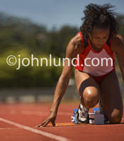 This picture of a woman track athlete in the starting blocks is a business metaphor for focus, concentration and preparation.
