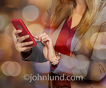 A woman uses a cell phone in a photomontage of city lights at night in a stock photo about mobile connections, cloud computing, and social media.