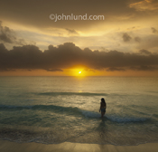 In a romantic vacation photo a woman wades into the warm blue-green tropical waters of an ocean at sunset or sunrise.