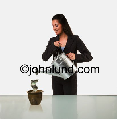 Stock picture of a woman watering a dollar bill being grown in a pot. It's a large metal sliver colored watering can and she is happy and smiling as she nurtures her investments.