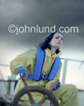 Pictures of a strong woman at the helm of a Sailing Vessel in a Stormy Sea showing skill and determination. Confident woman is wearing yellow rain gear and is steering the boat.