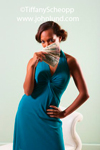 Black woman, a beautiful model, is coyly fanning herself with a handful of cash, yes, good old greenbacks.  She is wearing a beautiful blue dress and is very sexy.