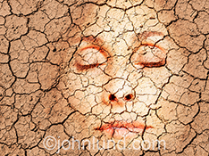 A beautiful woman's face is seen through dray cracked earth in a stock photo about health, beauty and skin issues...particularly dry skin conditions and produ cts and routines that can moisturize and sooth a woman's skin.