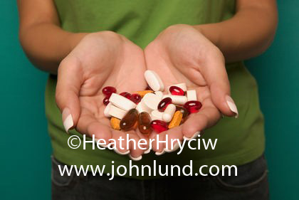 Picture of a womans hands holding a handful of various drugs, pills, capsules, gell tabs, and medications. Perscription drugs.  Close up photo of a woman holding a double handfull of perscription medications.  Vitamins. Torso hands, and pills only.