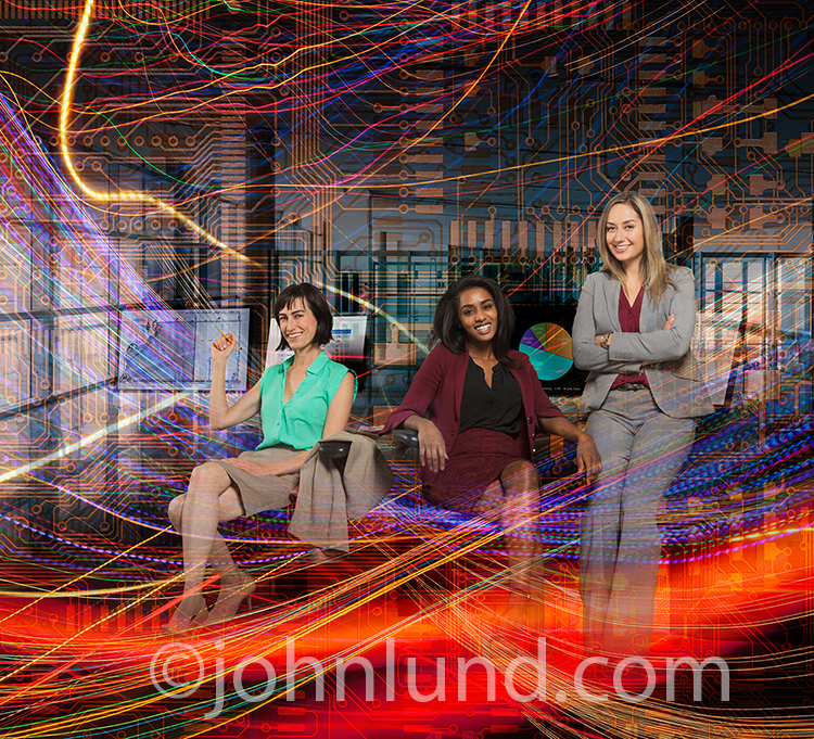Successful women in technology are shown in this stock photo featuring three women in a business setting multiple exposed with computer circuitry and vividly colored light trails indicating everything from big data to bandwidth to streaming data.