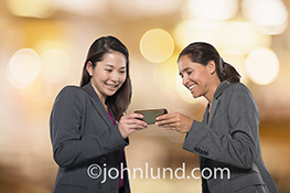 Two women share using social media over a mobile device in a stock photo about connection, sharing, and communications technology.
