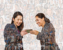 Two women share a mobile device against a backdrop of social media portraits in a stock photo about social networking, friendship and mobile connections.