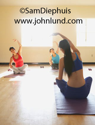 Picture of a group of middle aged women taking a class in Yoga. The yoga instructors back is toward the camera. She is wearing blue pants and a blue halter top. The women have one hand on their knee and the other in the air.