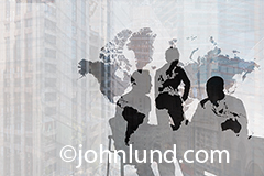 Three businesspeople in a meeting are silhouetted and seen through a graphic of a world map in an image about global business, international strategies and the importance of face-to-face meetings.