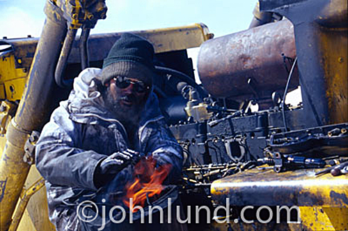 Picture of an Indian army mechanic in the Himalaya Mountains repairing a bulldozer in winter.